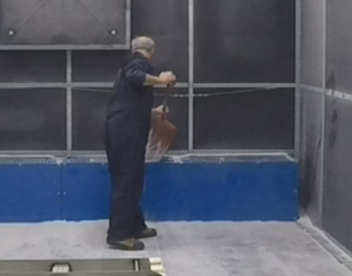 Man Shoveling Abrasive Media Into Excavated Above Ground Hopper