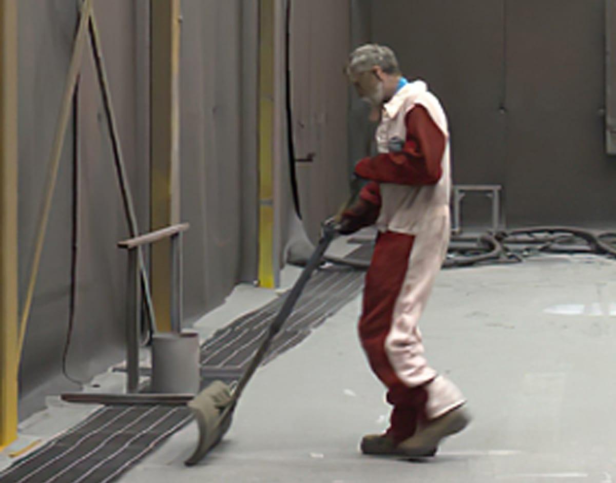 Man Shoveling Abrasive Media Into Excavated Floor Hopper